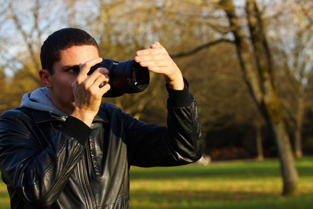 Fotograf deckt Objektiv mit der Hand ab
